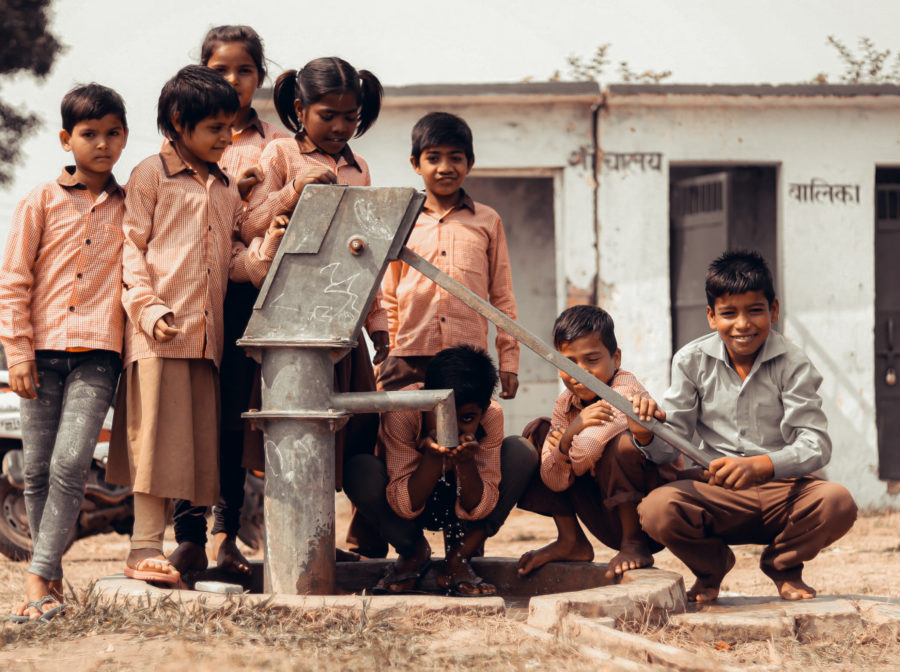 Children stand next to a water pump in a village in India.