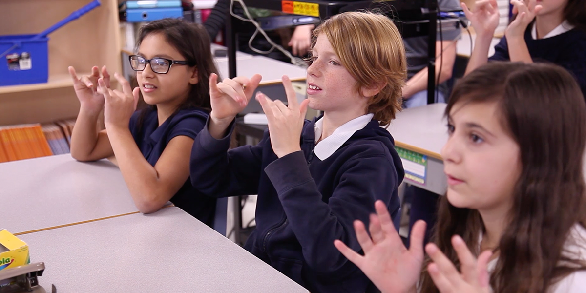 Students learn American Sign Language from an instructor at Silent Voice