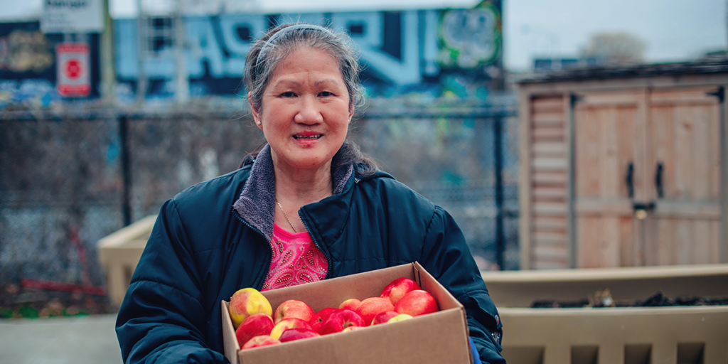A volunteer from LA Centre for Active Living holds a box of apples