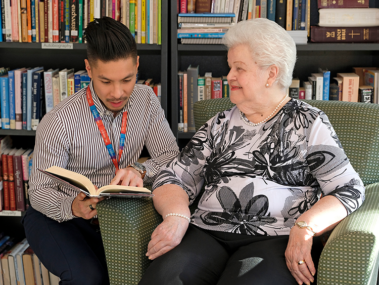 A resident of the Cardinal Ambrozic Houses of Providence reads with a volunteer