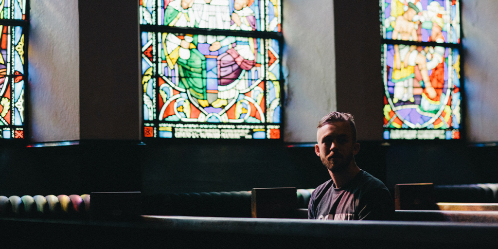 A young man prays in a church